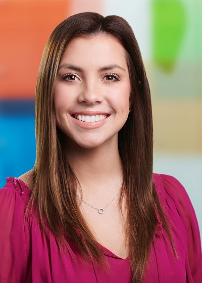 Genevieve Sheridan is smiling in front of a colorful, blurred background. She is wearing a pink top and silver necklace.