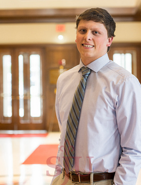 Tyler Whitten is standing in the Haub Business School lobby. He is wearing a pale blue shirt and striped tie.