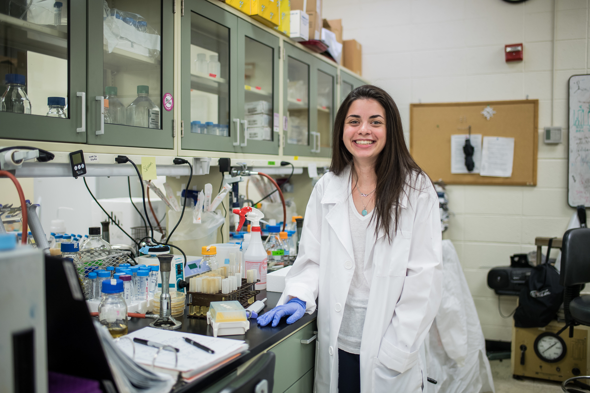 Marisa Egan is smiling while standing next to a counter in a lab. She is wearing a white lab coat and rubber gloves.