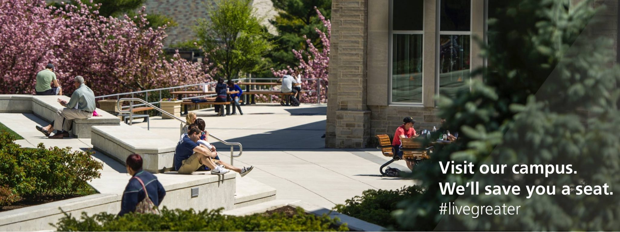 "Students sit in the sunshine through the SJU quad. The screen reads, ""Visit our campus. We'll save you a seat. #livegreater"""