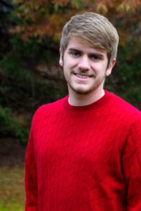 Charles Gallagher wears a red sweater and smiles before a canopy of changing fall leaves.