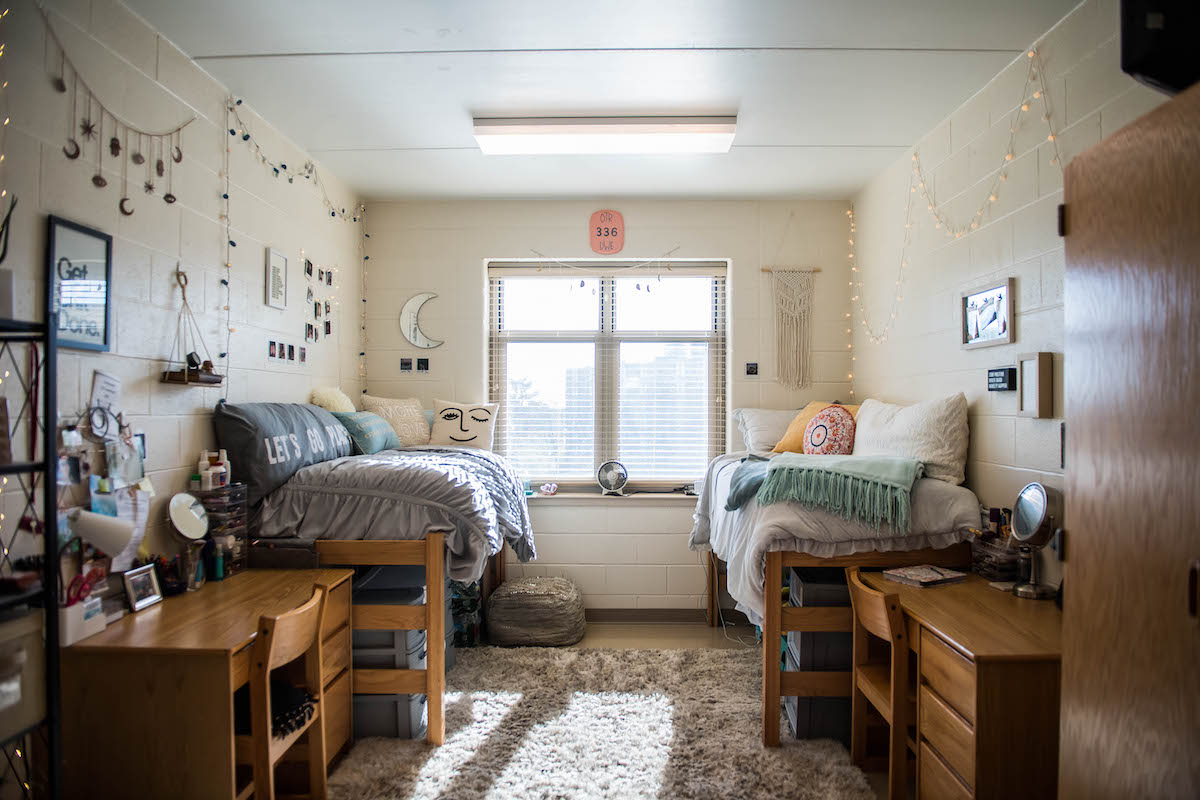 A dorm room shows two beds and desks with the light coming through the window.
