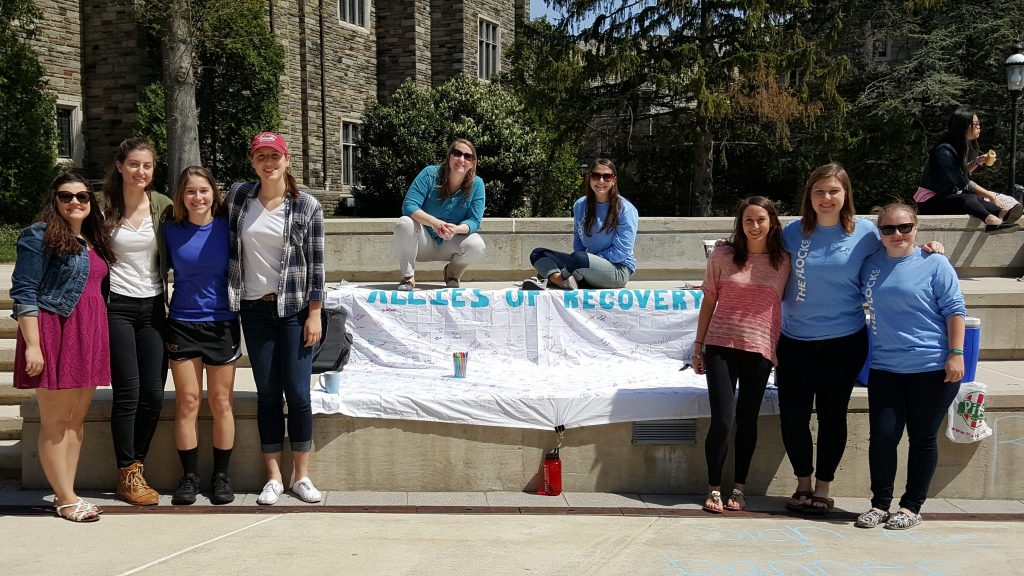 students standing over an allies of recovery banner